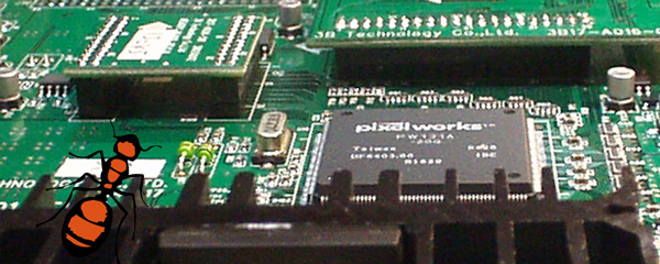 An ant perched on top of a QFP heat sink looks down at a pc board.